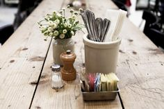 Silverware is stored in stoneware jars, vintage baking tins house sachets of sugar, and stoneware mustard jars hold flowers at Joan's on Third