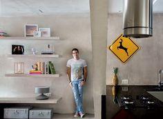 Living | O morador Marcelo no corredor que une sala e cozinha. Na parede, pintura de concreto e prateleiras de alvenaria – a de baixo serve banco (Foto: Denilson Machado/MCA Estúdio)