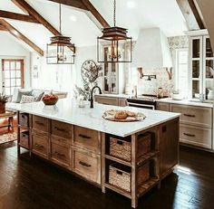 Offene Küche aus Holz mit mittiger Kücheninsel in altem Haus. Lichtdurchflutete Küche im Landhausstil mit weißer Arbeitsplatte aus Stein. Passende Küche für freiliegende Deckenbalken aus Holz. Inspiration für Küchen Renovation