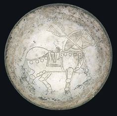A SASANIAN SILVER BOWL  CIRCA 6TH-7TH CENTURY A.D.  The interior incised with a stockily-built, caprisoned, high-stepping horse, with left foreleg raised, with saddle and saddle blanket, reins and bridle, the trappings decorated with circular phalerae, a ribbon tied around the neck, the ends fluttering behind, the tail also tied, with traces of gilding