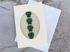 A small handmade card: 3 1/2 by 5 1/2 inches (just under 9 cm x 14 cm)    An original cross stitch design made and stitched by me.