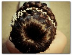 Braiding spiraled around the bun with a beautiful diamonte vine pinned onto the hair completing the look. www.bridalandpromhairdesign.com