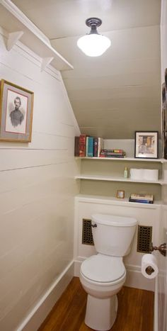 Here is a powder room under the stairs and a older house. It's a fairly basic design but looks good with the white walls and ceiling along with the wood floor.