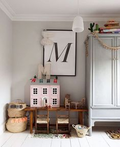 I just love the corner of this kids' room!! Grey armoire plus framed M art and vintage dollhouse