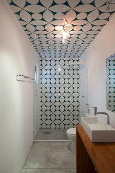 Geometrische tegels vormen een pad van douche tot plafond.