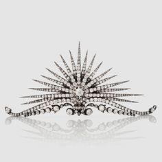 A substantial diamond sunburst tiara, made by Faberge in Russia, 1907. Featuring no fewer than nineteen radial diamond arms, and rising from a double band of elongated diamond scrolls.