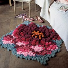 Carpet shaped flowers with multicolored pompoms attached to a canvas
