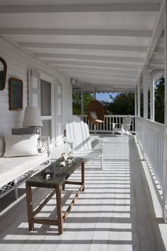 coastal styled whitewashed porch with a wicker hanging chair