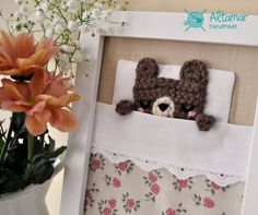 Measures: Frame 15 x 20.5 cm (6x 8)  Fabric and wool picture that simulates the bed of a small bear sleeping. Perfect for decorating childrens rooms.   The bed has a beige sheet, a small white pillow, a white sheet topped with a lace and a a beige quilt with a pattern of pink flowers. A small handmade crochet wool bear is sleeping inside the bed.  The frame is made of wood fibers and you can choose white or wood color. You can hang it on the wall or support it on any surface, upright.  It…