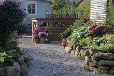 Garten Gestaltung naturnah Schotter Holz Natursteine Gemüsegarten Sträucher Stauden Rundholzsichtschutz