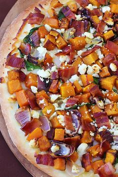Butternut, bacon, spinach, & feta pizza. 1 butternut squash, peeled, cored and diced into 1/2″ cubes  1 small red onion, peeled and quartered  4 Tbsp. olive oil  kosher salt and freshly-ground black pepper  1 medium pizza crust  1 cup shredded Mozzarella cheese  2 cups loosely-packed baby spinach  6 slices lean bacon, cooked and diced into 1/2″ pieces  1/3 cup crumbled ATHENOS feta cheese