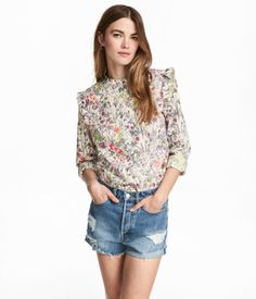 Natural white/floral. Long-sleeved blouse in woven cotton fabric with a small stand-up collar. Button placket, ruffle trim on shoulders, and gently rounded