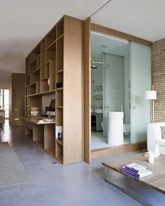 Full height sliding partition slides into pocket behind bookcase, Remodelista