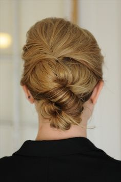 Love this hairstyle and it is super easy to do, especially day after washing. Pull back front and hair at crown (no part) after spraying (w/ P. Mitch. finishing spray.) Twist over and bobby pin it like a mini French twist. Then grab hair at nape and twist the entire length. Grab at halfway point and twist/curl up to form a little bun then pin like crazy and spray. Watch video for demo.