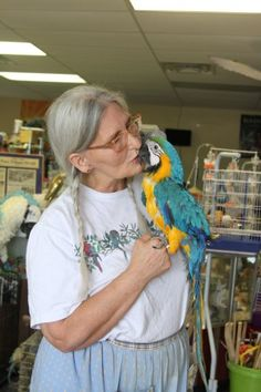 Ramona Parker plays with two of her birds, Buddy and Kasey, in her store Ramona's Parrots