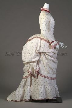 Ensemble Date1873-1877 CultureAmerican, attributed DescriptionWhite cotton printed with red circles. Bodice: fitted over hips, ruffled edge, long sleeves. Skirt: bustle with white cotton and red trim. Overskirt: as draped apron.