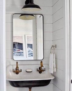 Love this black trough sink with aged brass faucets and shiplap walls