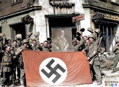American soldiers of the 274th or 275th Inf. Regt., 70th Infantry Division of the US 7th Army display a Nazi flag and a portrait of Adolf Hitler, outside of a cafe in Hohenzollernstraße, Saarbrücken, Germany after the capture of the city on the 22nd of March 1945. (Photo by Horace Abrahams/Keystone/Getty Images). (Colourised by Royston Leonard)