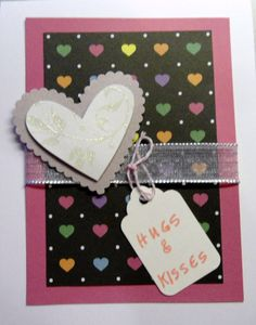 """Colorful heart paper backed by a piece of pink cardstock and topped with a purchased raised glittery heart - tied together with a silvery ribbon and an added tag with """"Hugs & Kisses"""" - a Valentine for the grandkids..."""