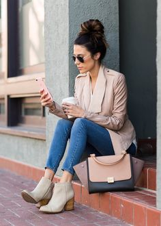 A blush leather jacket, skinny jeans, and ankle boots paired with a colorblock satchel