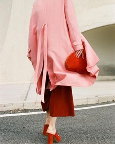 Flowy bubblegum pink trench coat, draped over dark red cropped culottes, crimson suede slide heeled mules, and a red leather zip-top half-moon clutch, all by Mansur Gavriel.