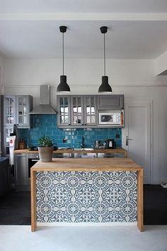 Carreaux de ciment blanc et bleu à motifs ronds et arrondis. Pièce avec deux lampes suspendues noires, cuisine avec plan de travail en bois hêtre avec carrelage mural bleu clair.
