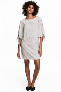 Short, straight dress in a viscose crêpe weave with wide, flared sleeves with a slit and tie. Unlined.