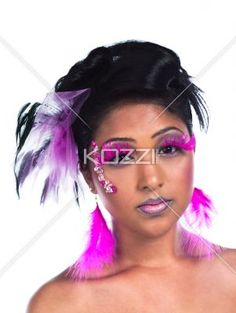 portrait image of a attractive woman wearing pink eyelashes and feather earrings. - Close-up shot of a beautiful young female wearing pink feather earrings and pink false eyelashes over plain white background. Model: Ravia Hosein Hair, MUA and Sylist: DMG Designz -  Jewellry Provided by Unique Rainbow