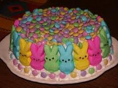 """Oh my gosh. The most colorful Peep cake yet! This one is made from two 9"""" round cakes. Apply your frosting- they have used white buttercream. Then, place your Peep bunnies to where the top of their ears come to the edge of the top of the cake. Then, decorate the top and underneath of the Peeps with pastel Easter M's. Fun for the kids!"""
