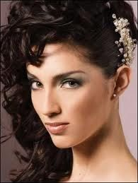 Curled updo pulled over to the right of the head with flower clip on side