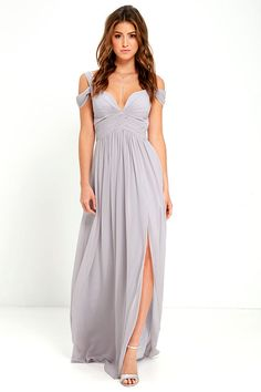 "From posh prom or lavish cocktail party, and from sea to shining sea, the Bariano Ocean of Elegance Grey Maxi Dress will have you in the lap of luxury wherever you may go! Crisp grey Georgette starts this exquisite ensemble off with tank straps (joined by sheer off-the-shoulder straps) that support a fitted bodice with a plunging sweetheart neckline, and elegant ruching details. Additional ruching delicately encircles an empire waistline, while a floor-length maxi with a stunning 31"" side…"