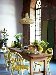 love the yellow chairs, the natural wood light and table and the green plants and bottles