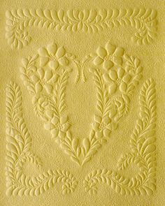 "Whole-cloth quilt made from buttery yellow Dupioni silk, 16x20, by Kim Buzolich. The center heart pattern is from a book called ""The Heirloom Nursery""."