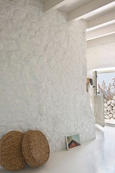 A glimpse inside the all-white interior of Sterna, an artists residence on the Greek island of Nisyros. Just beside the traditional woven baskets is an artwork left behind by one of the artists who visited the house. Photo by: Montse Garriga Grau