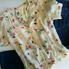 """FINAL PRICE UO by PINS AND NEEDLES   SHEER TOP * Feminine touches all over the place!  * Pleated detail near shoulders, on hem and aleeves * Sheer ivory shell with muti-colored florals * Functional buttons down front * Dress it up or down easily * True to size * 3rd pic shows minor flaws which are hidden by the pleats on outside but I like to disclose everything  * Otherwise great condition!   Bust 37-38""""   Waist 34""""  Over 170 items listed so bundle to save more! Ask for a quote anytime…"""