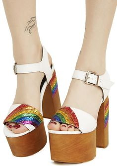 Sugar Thrillz Chasing Rainbows Platforms that pot of gold is yerz, bb! Taste the rainbow in these platformz that feature a brown wood sole, white vegan leather straps at the toes and ankle, and glorious glittery rainbows archin' across yer toes and on da heel.