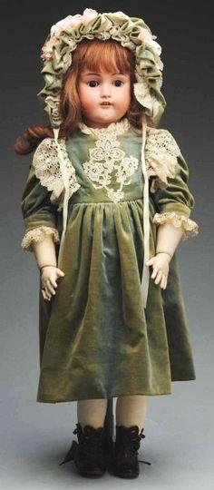 Porcelánová panenka * v zelených sametových šatech, zdobených krajkou a čepečku.