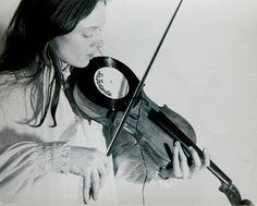 """vinylespassion:  Bob Bielecki - A young Laurie Anderson playing her own invention the Viophonograph, 1977. Artiste pluridisciplinaire et expérimentatrice, musicienne, performeuse, plasticienne, Laurie Anderson a mis au point le """"viophonographe"""", une platine montée sur un violon, avec une aiguille fixée dans l'archet."""
