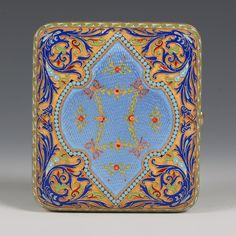 A magnificent Russian silver gilt and enamel cigarette case, Grachev, St Petersburg, circa 1904-1908. Of rectangular form with rounded corners, the case decorated with shaped lozenges enameled in a translucent powder blue over an engine turned ground with red and green colored gold paillons of ribbon-tied floral swags, the border with scrolls against a gilded stippled ground, gilt interior.