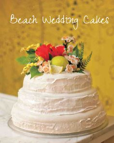 25 Amazing Beach Wedding Cakes | Martha Stewart Weddings - This bride and groom were having so much fun at their reception that they forgot to cut this three-tier coconut cake topped with tropical antique fabric flowers, red hibiscus flowers, lime slices, and greenery designed by Bonito.