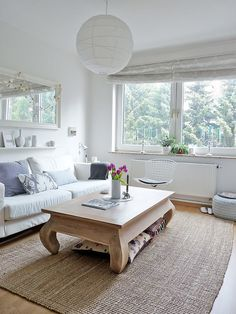 Adorable coffee table. Lots of white, wall shelf with mirror above, plants in the windowsill. ♥