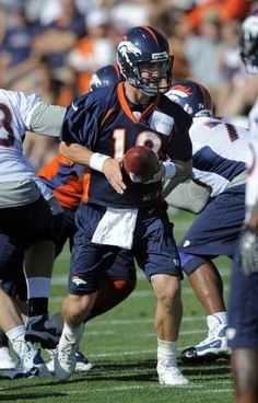 Denver Broncos quarterback Peyton Manning looks to hand off during the opening session of Denver Broncos NFL football training camp in Englewood, Colo., Thursday, July 26, 2012. (AP Photo/Jack Dempsey)
