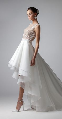 Elegant short dress with train. Skirt in floating organza and crinoline. Sleeveless bodice in tulle and precious embroidery. Waist highlighted by bands to create a young look.