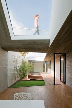 A courtyard garden divides the two sides of this concrete house in Vienna, which has been squeezed onto a plot just five metres wide.