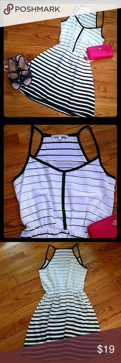 Black and White Racer back dress size small Pretty black and white Collective Concepts dress. Size small.  Racer back. Elastic at waist to give you stretch. Slightly high low style. Really cute if you put a bright pink or blue belt with it.  Top area is slightly sheer.  There is a fine little black line on the front. Please refer to the photo. I have not tried to wash it out it may simply be a pencil mark.  Besides the little line this dress is in great condition and ready to wear…