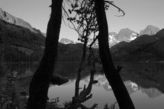 """Shadow Lake remains shrouded as the morning sun hits the mountains beyond.  """"The ansel Adams Wilderness"""" by Peter Essick"""