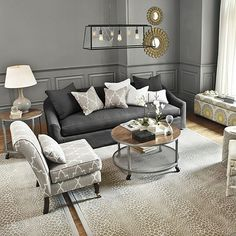 Room from Ballard Designs -- charcoal sofa with upholstered accent chair and animal-print rug. LOVE!