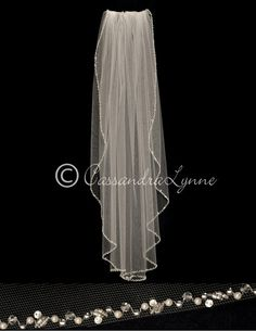 A small wavy edge of pearls, crystal beads, rhinestones and beads adorns this classic wedding veil. It is fingertip length at 36 inches and 72 inches wide, on a