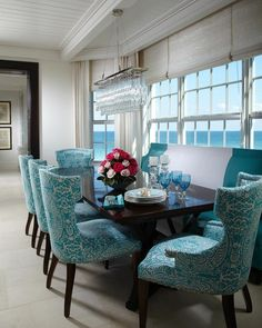 Natural light and a gorgeous ocean view flood in the large windows in this tropical dining area. The aqua patterned dining chairs add lively color and texture to the space.
