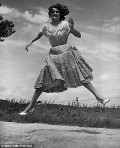 Italian actress Sophia Loren looks delighted as she's captured airborne in a field
